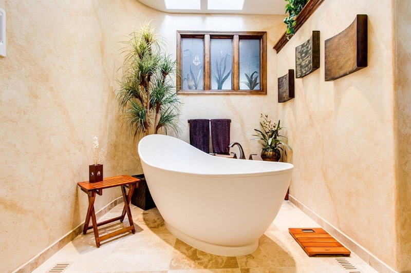 A bath tub in the center of a bathroom with plants