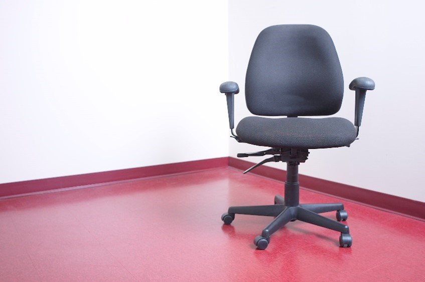 An ergonomic office chair on a red floor.